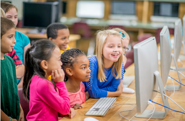 Group of children using a computer, looking at the display